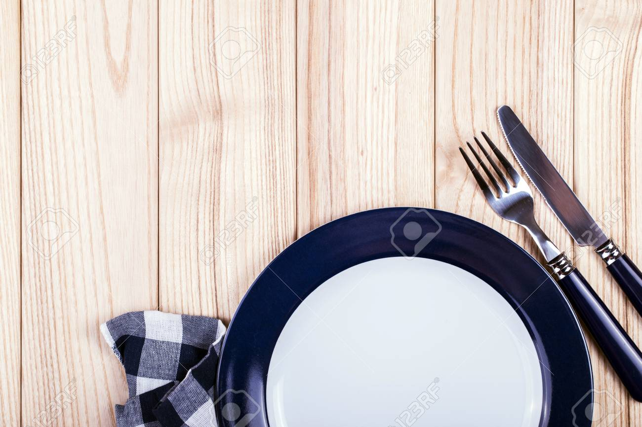 Empty dish, knife and fork and blue napkin on wood table - 40863322