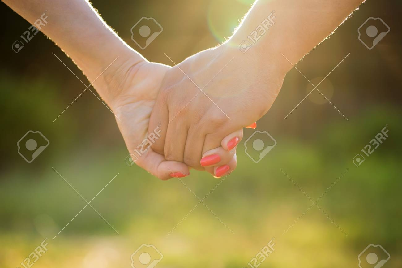 Concept shoot of friendship and love of man and woman: two hands over sun ray and nature - 41259788