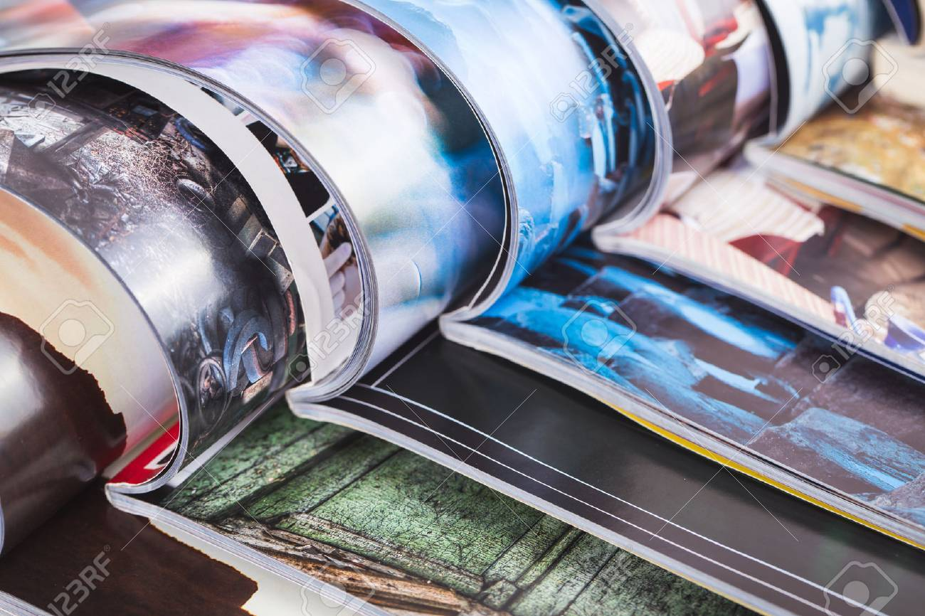 stack of open colorful magazines - 44589720