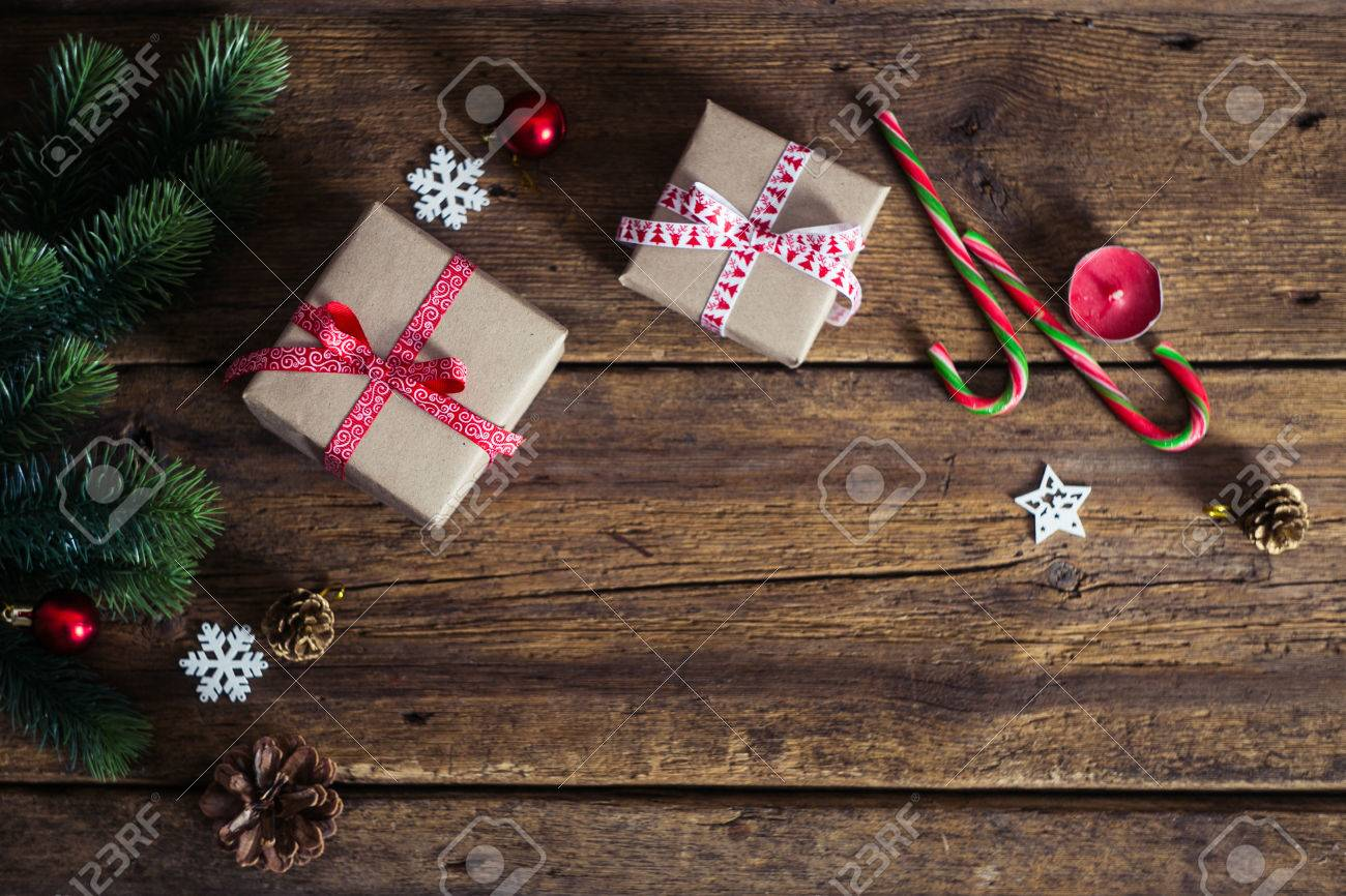 Christmas presents on a wooden background with candy cane, fir branches, candle, cones. - 48977724