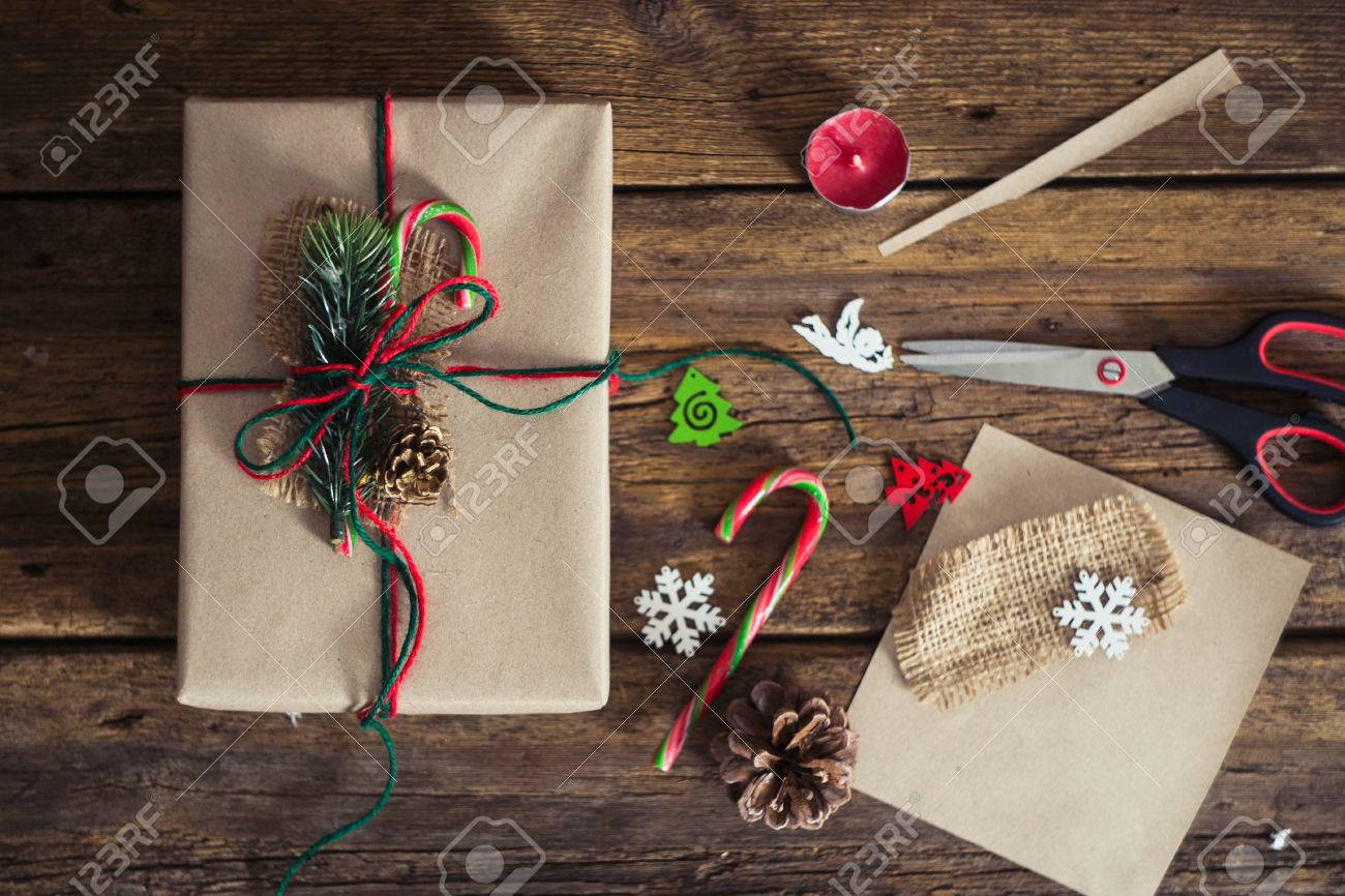 Christmas gift box on a wooden background with candy cane, fir branches, candle, cones. - 49077708