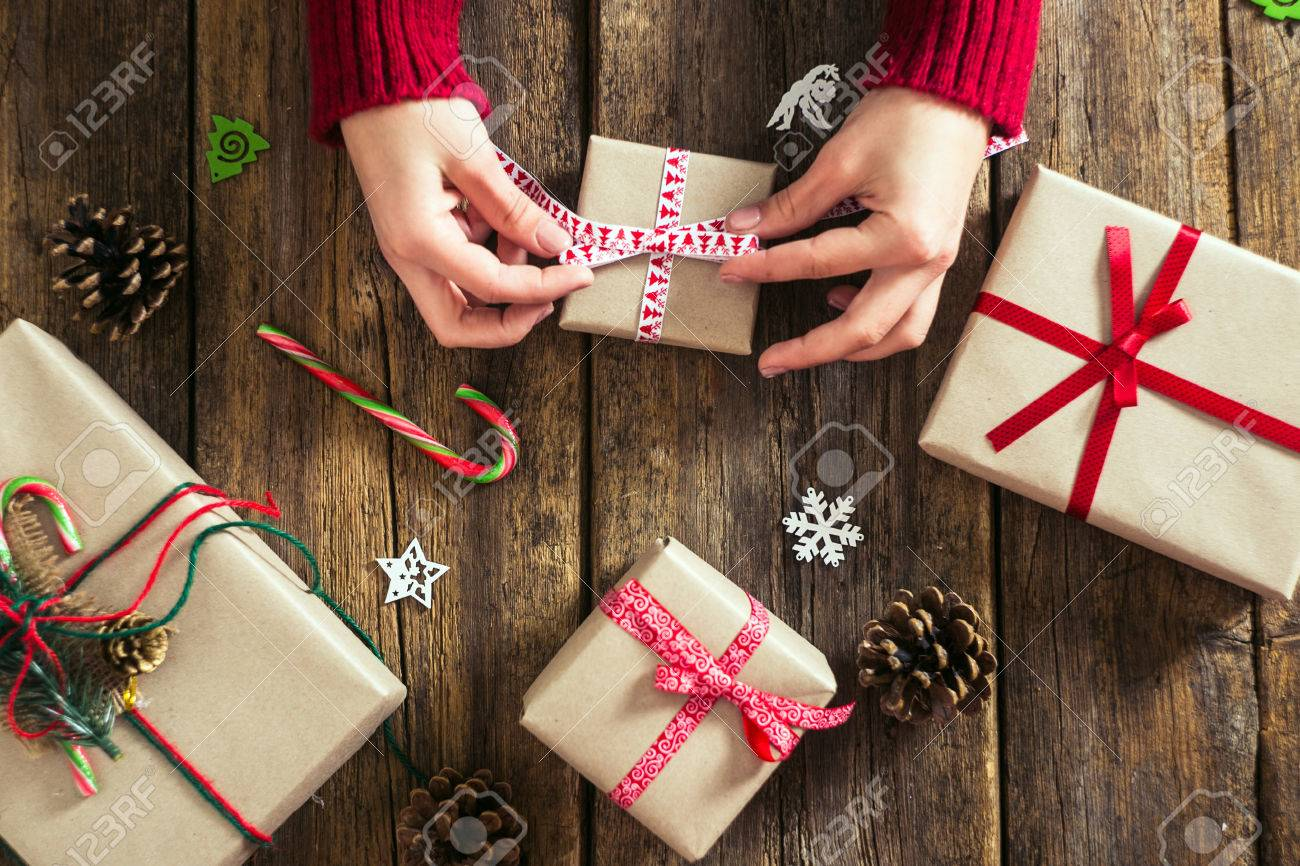 Male hands wrapping xmas gifts into paper and tying them up with red threads - 49077915