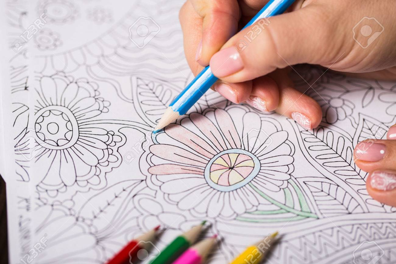 Girl paints a coloring book for adults - 51638571