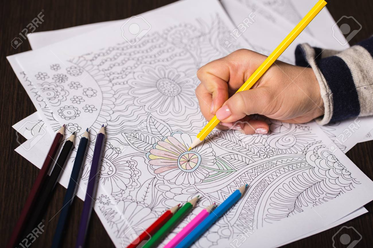Girl Paints A Coloring Book For Adults With Crayons Stock Photo ...