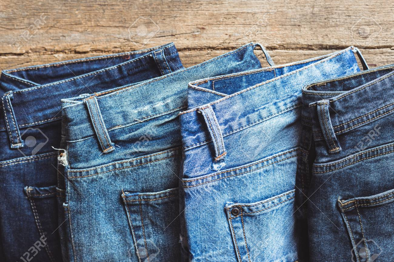 Jeans stacked on a wooden background - 100550511