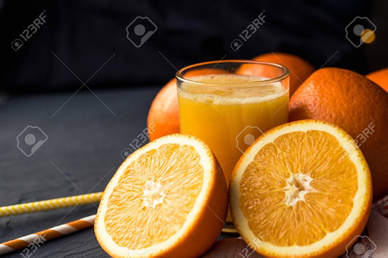Fresh orange juice and fresh fruit oranges on a black background - 119103145
