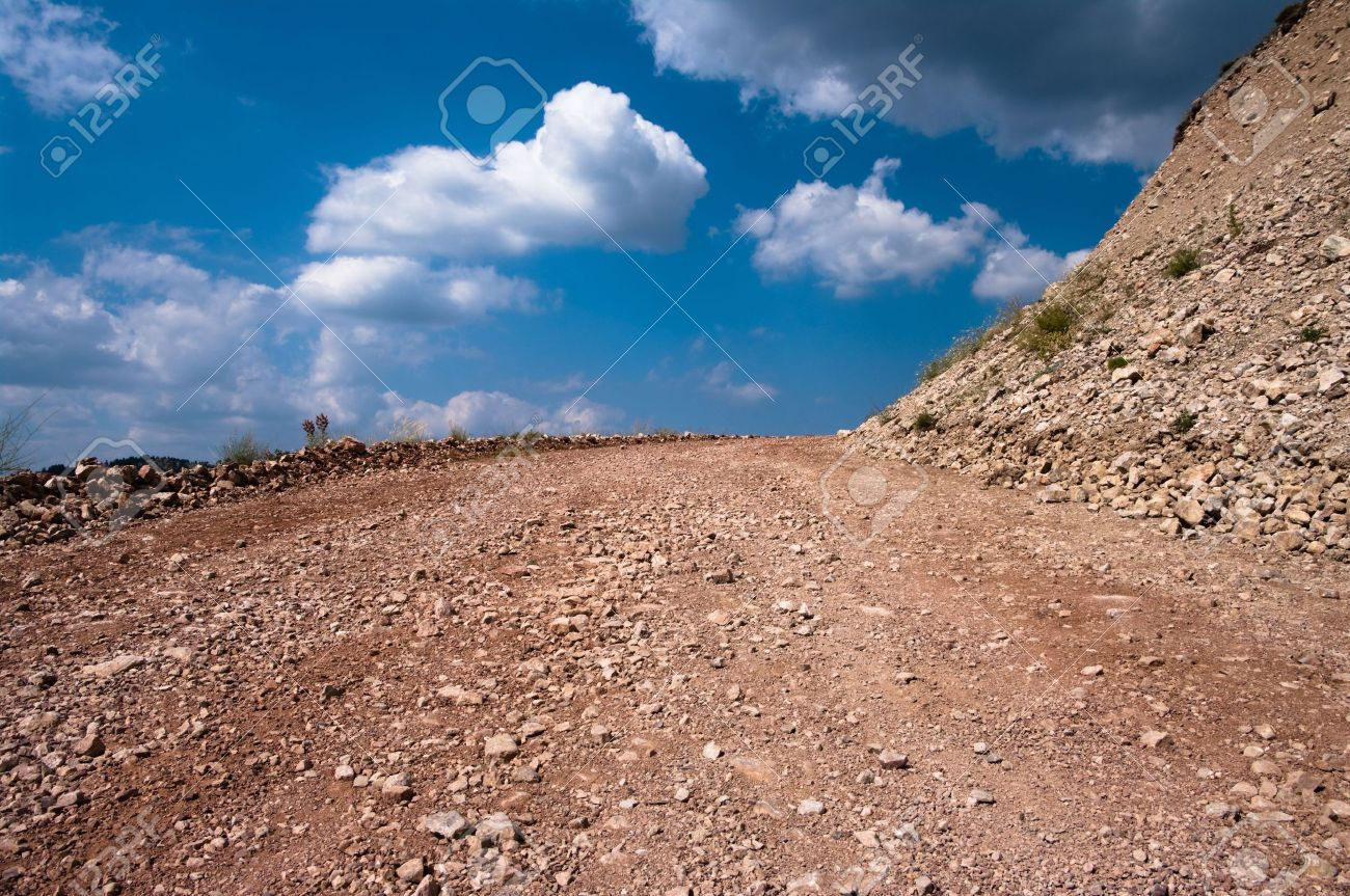 dirt road of rocky ground on background clouds in blue sky Stock Photo - 5679885
