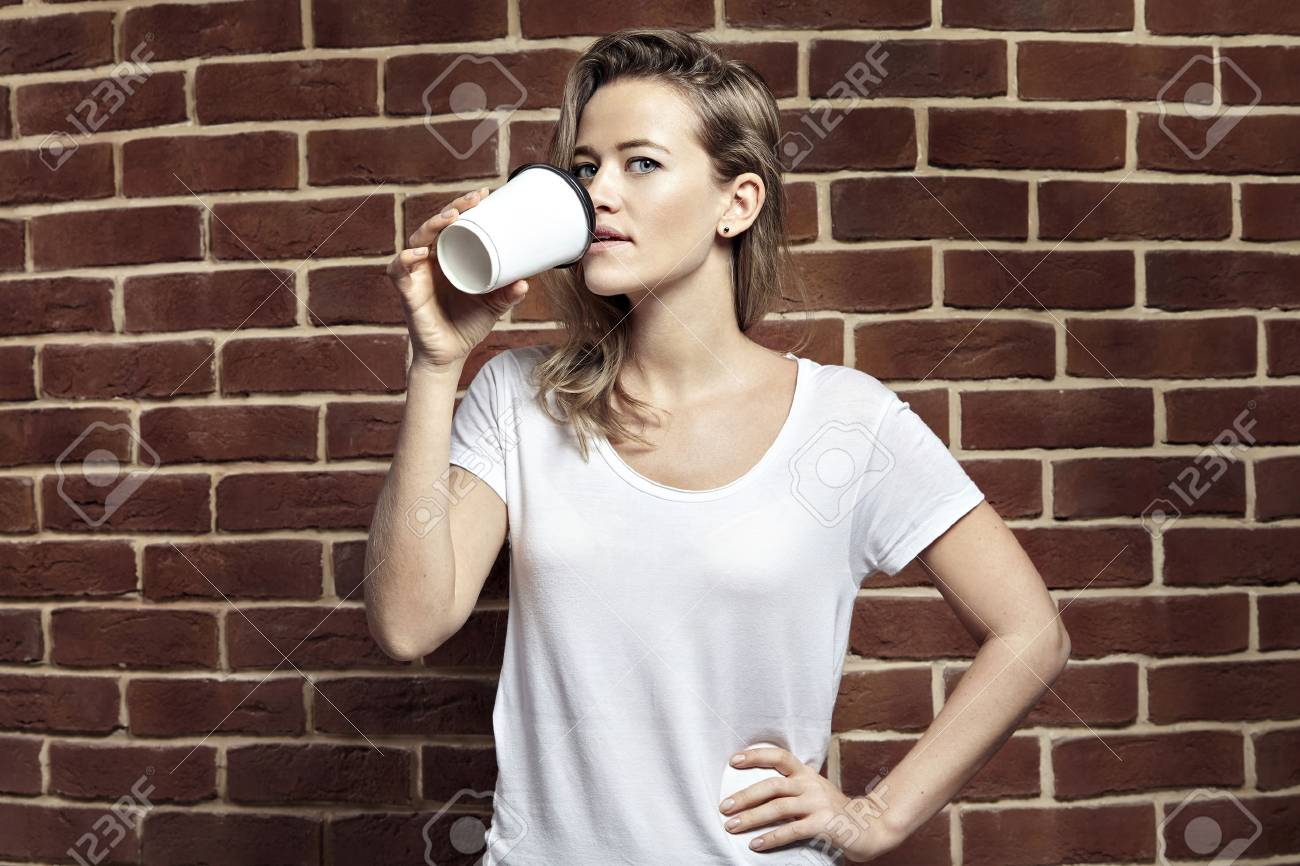Beautiful blonde woman drinking coffee in paper blank cup takeaway beautiful blonde woman drinking coffee in paper blank cup takeaway wearing white t shirt voltagebd Images