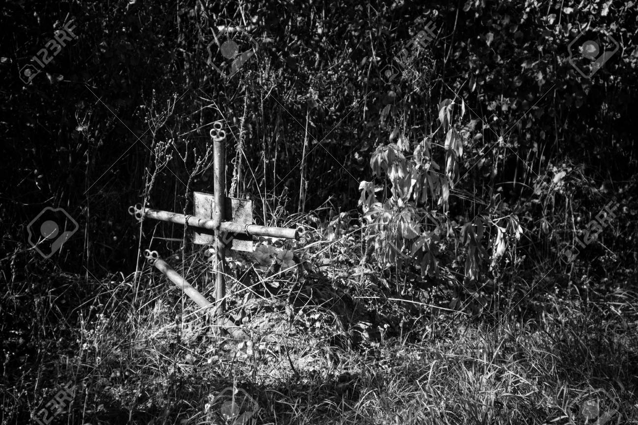 Old cross in graveyard black and white tone