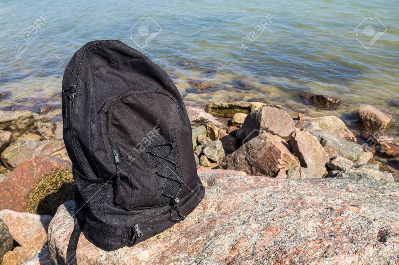 Stock Photo - Tourist or traveler backpack on rock with sea shore  background. Summer vacations concept 1e16e49e7d201