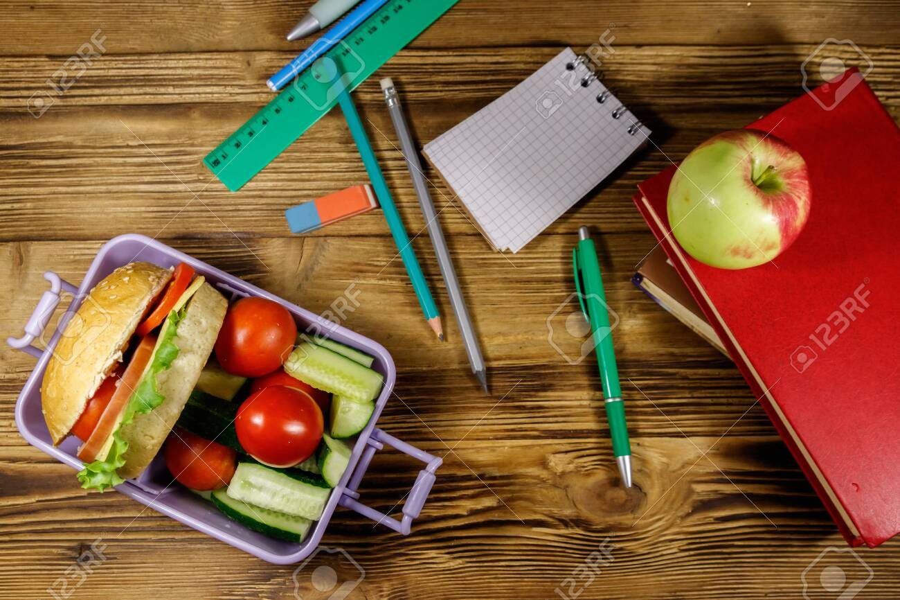 Back to school concept. School supplies, books, apple and lunch box with burgers and fresh vegetables on a wooden table. Top view - 130418934