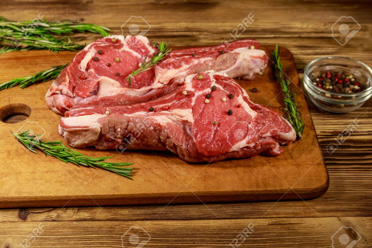 Raw fresh beef rib eye steaks on bone with spices and rosemary on wooden table - 137244924