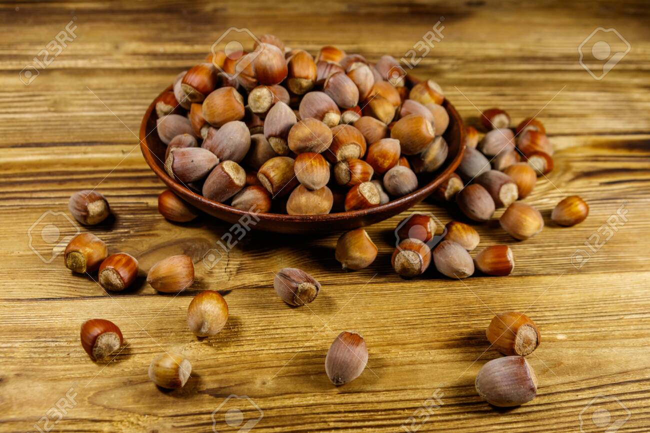 Hazelnuts in ceramic plate on a wooden table - 141974574