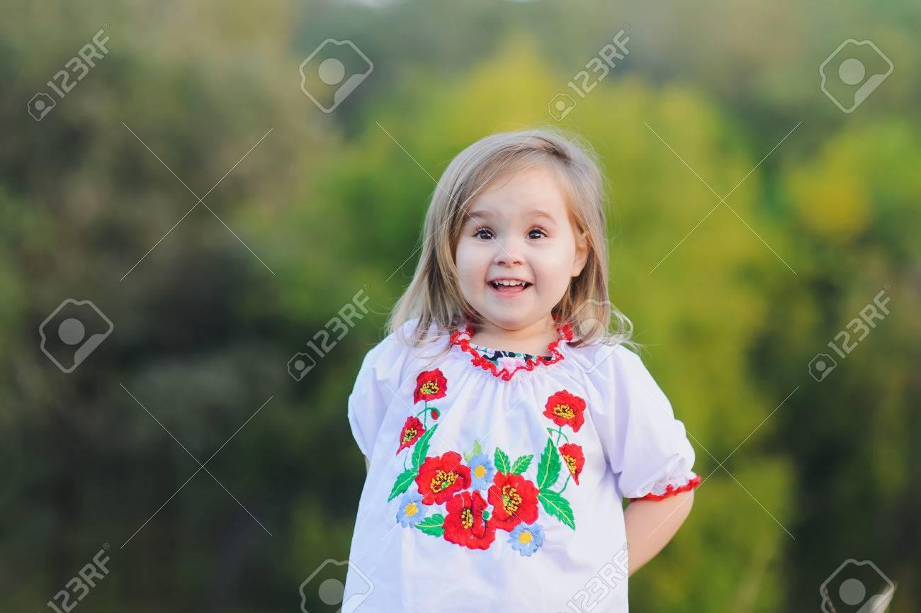 kleine 3-jährige mädchen freut sich emotional. ein mädchen im weißen  ukrainischen nationalen kleid mit aufgestickten blumen gekleidet.