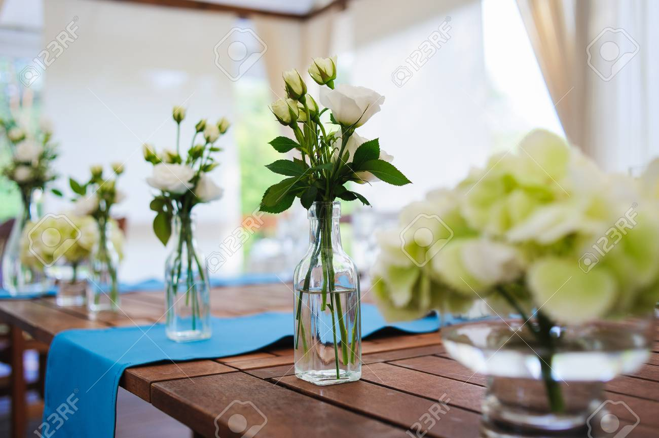 White roses in glass bottles and vases on wooden table wedding stock photo white roses in glass bottles and vases on wooden table wedding decorations rustic style junglespirit Image collections