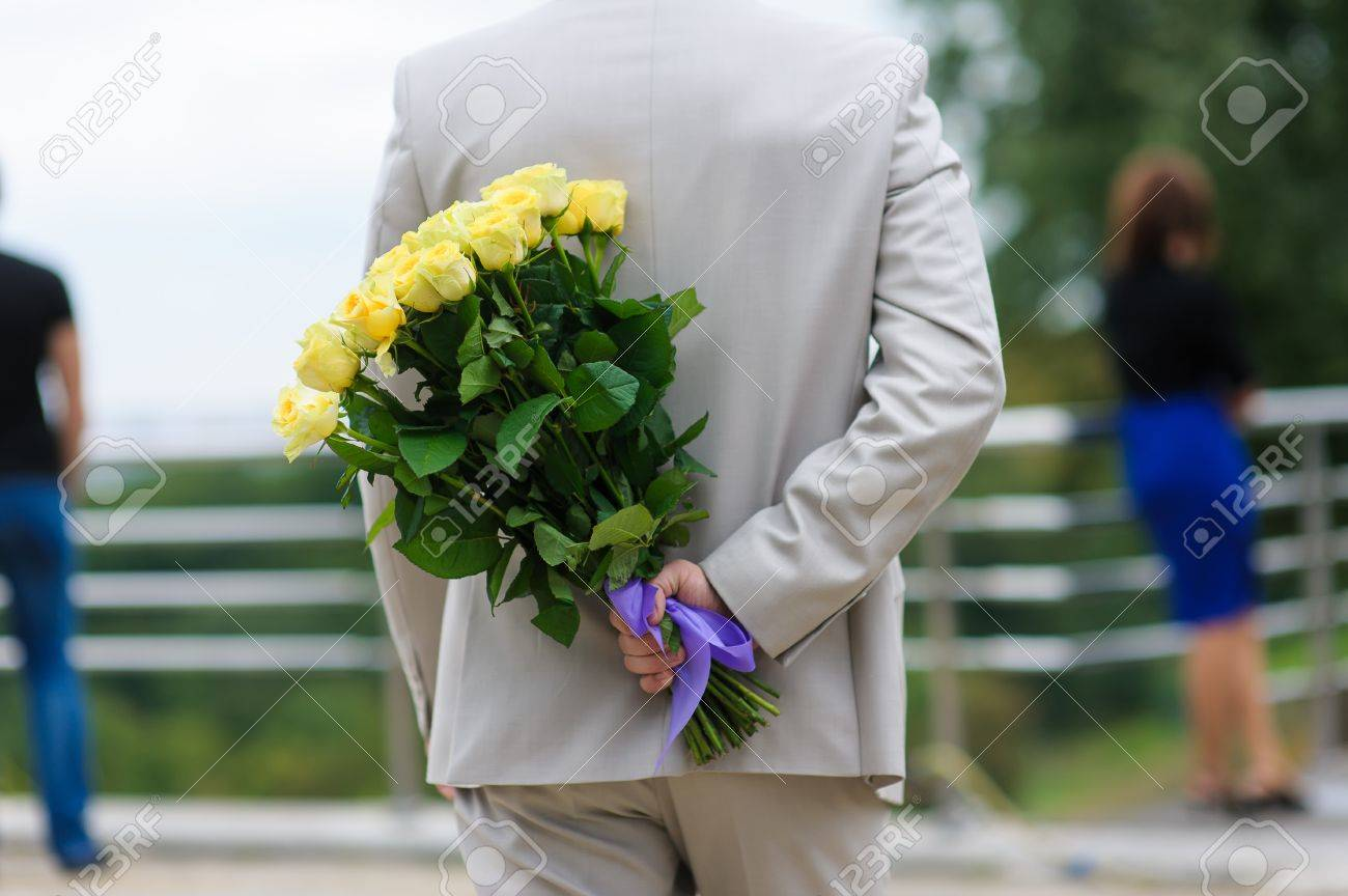 Young Man Hides A Bouquet Of Flowers Behind His Back. Yellow.. Stock ...