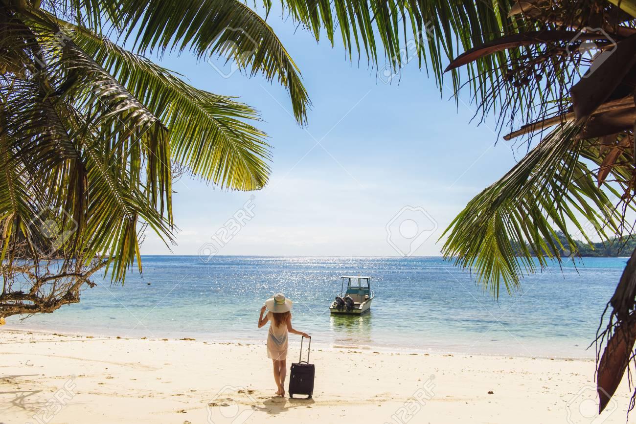 Mujer Joven Con Sombrero Y Maleta En La Playa. Ropa Transparente ...