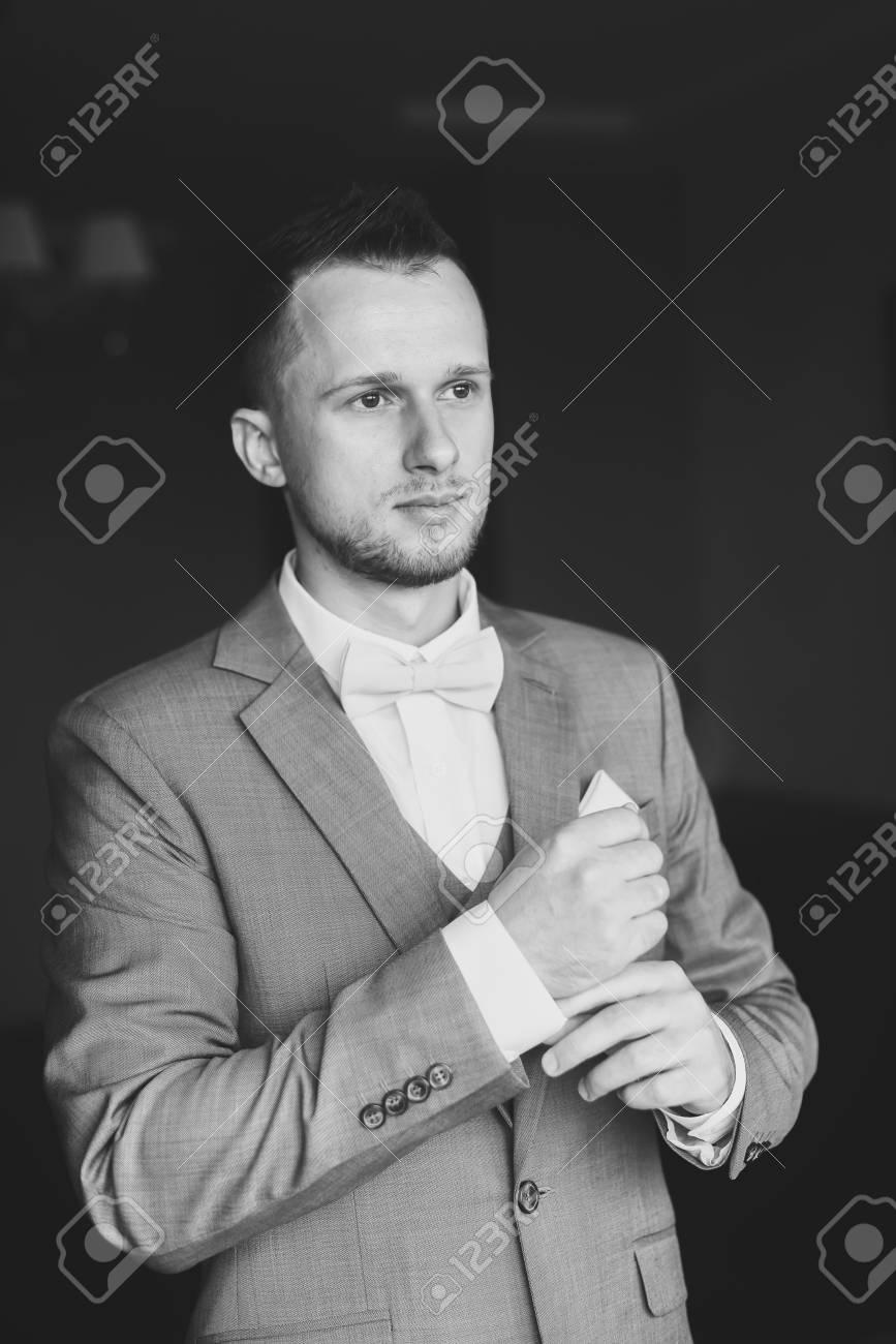 vente la moins chère haut de gamme pas cher style roman Légant jeune homme de mode habiller pour la célébration de mariage. Beau  marié habillé en costume gris, chemise blanche et noeud papillon rose se ...