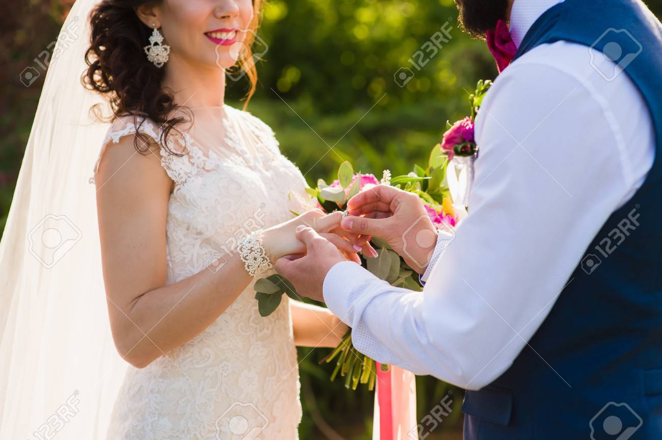 340834a1578e El Novio Usa El Anillo En El Dedo De La Novia. Los Recién Casados    intercambian Anillos En El Registro Del Matrimonio Al Aire Libre. Primer  Plano De Hombre ...