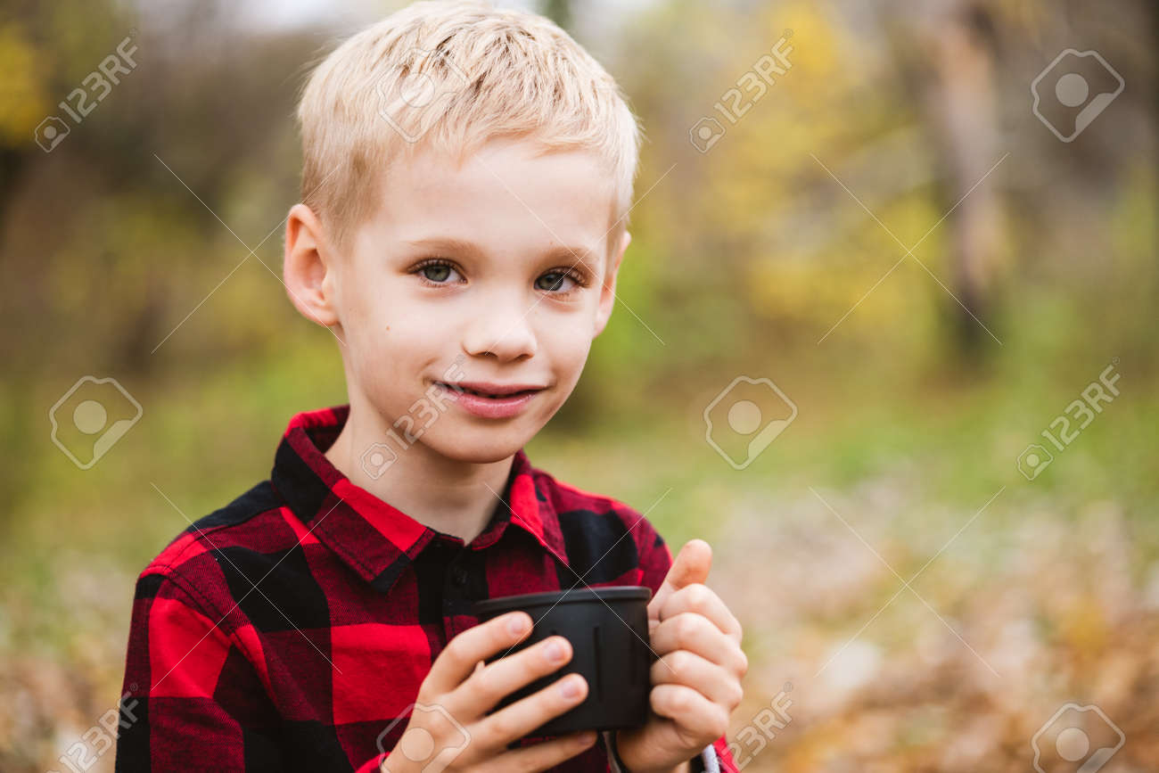 Preteen blonde male child in red shirt holds black bottle cup with hot beverage. Happy family weekend at autumn park. - 156863405