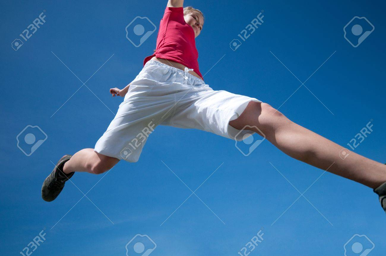 Beautiful young woman jump into blue sky on sunny summer day - 8593858