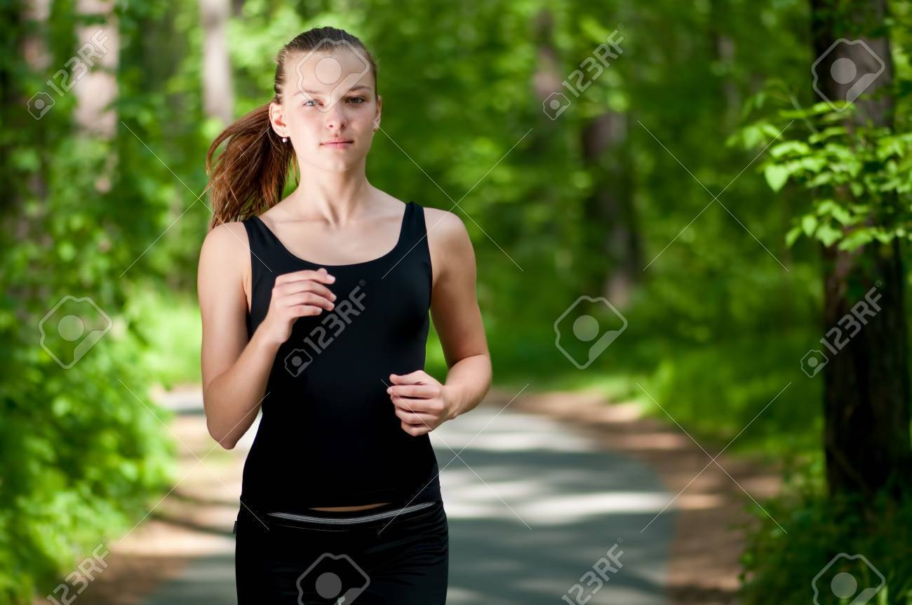 Beautiful young woman running in green park on sunny summer day Stock Photo - 8640288