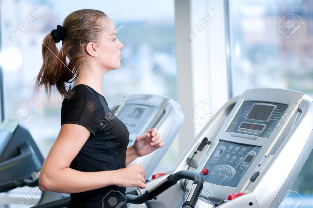 Young woman at the gym exercising. Run on on a machine. Stock Photo - 8715650