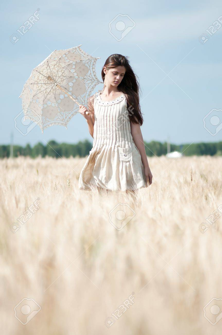 Beautiful sad and lonely woman with umbrella walking in wheat field. Timed. Stock Photo - 8708078