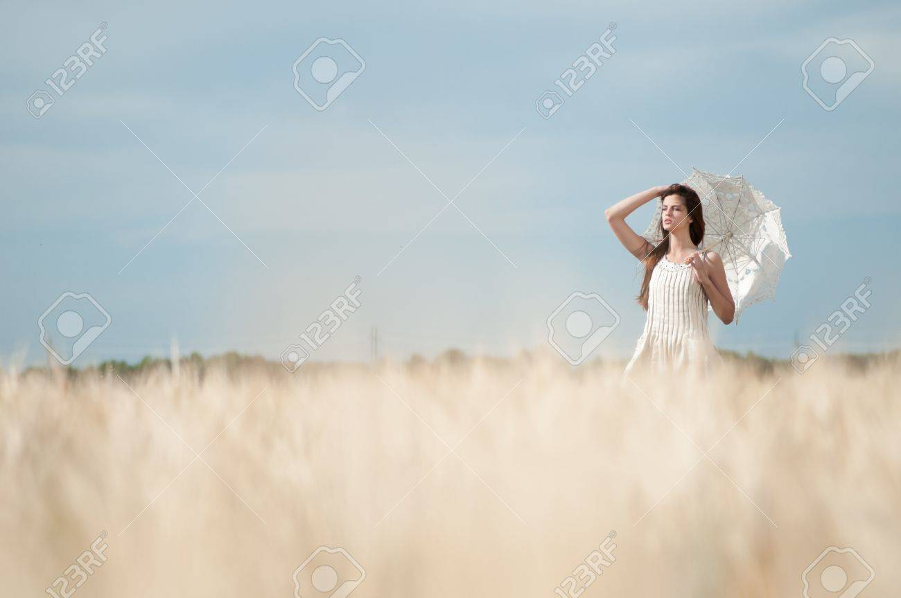 Beautiful sad and lonely woman with umbrella walking in wheat field. Timed. Stock Photo - 8715479