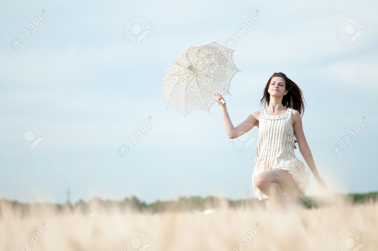 Beautiful sad and lonely woman with umbrella run in wheat field. Timed. Stock Photo - 8715447
