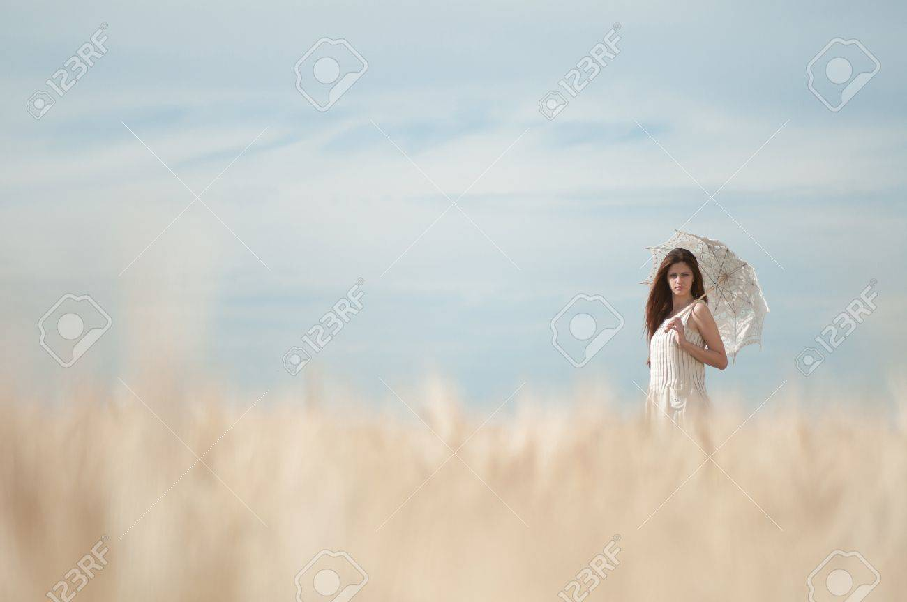 Beautiful sad and lonely woman with umbrella walking in wheat field. Timed. Stock Photo - 8876028