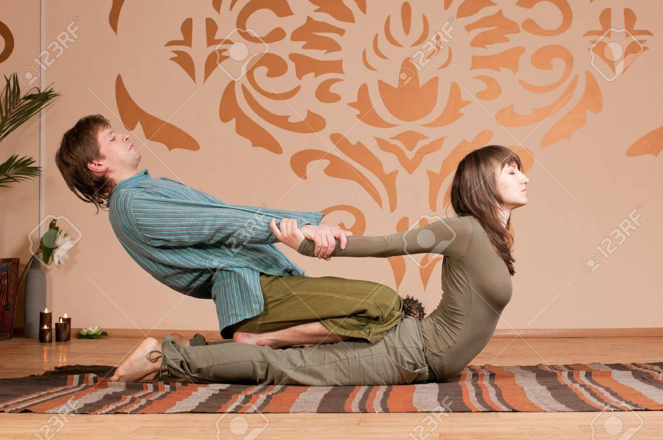 Two young man and woman couple doing yoga. Massage Stock Photo - 9293305
