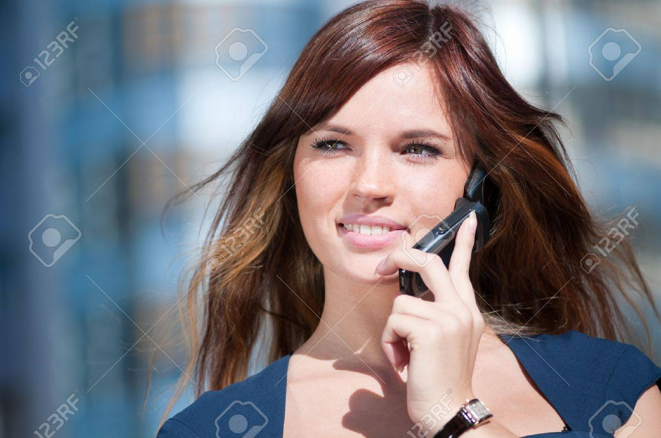 Young business woman using mobile cell phone over city background. Student Stock Photo - 9566351