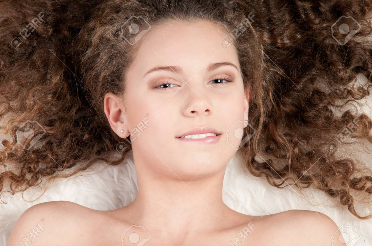 Closeup portrait of young emotional beautiful girl with perfect curly hair. Lying on white fur bed Stock Photo - 9633177