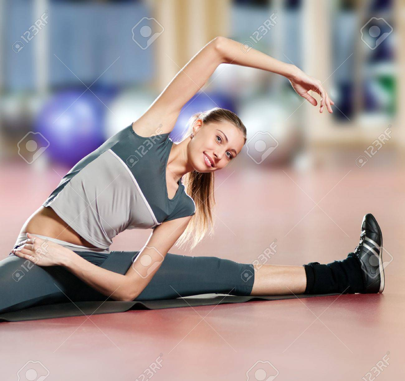 Beautiful sport woman doing stretching fitness exercise at sport gym. Yoga Stock Photo - 9805873