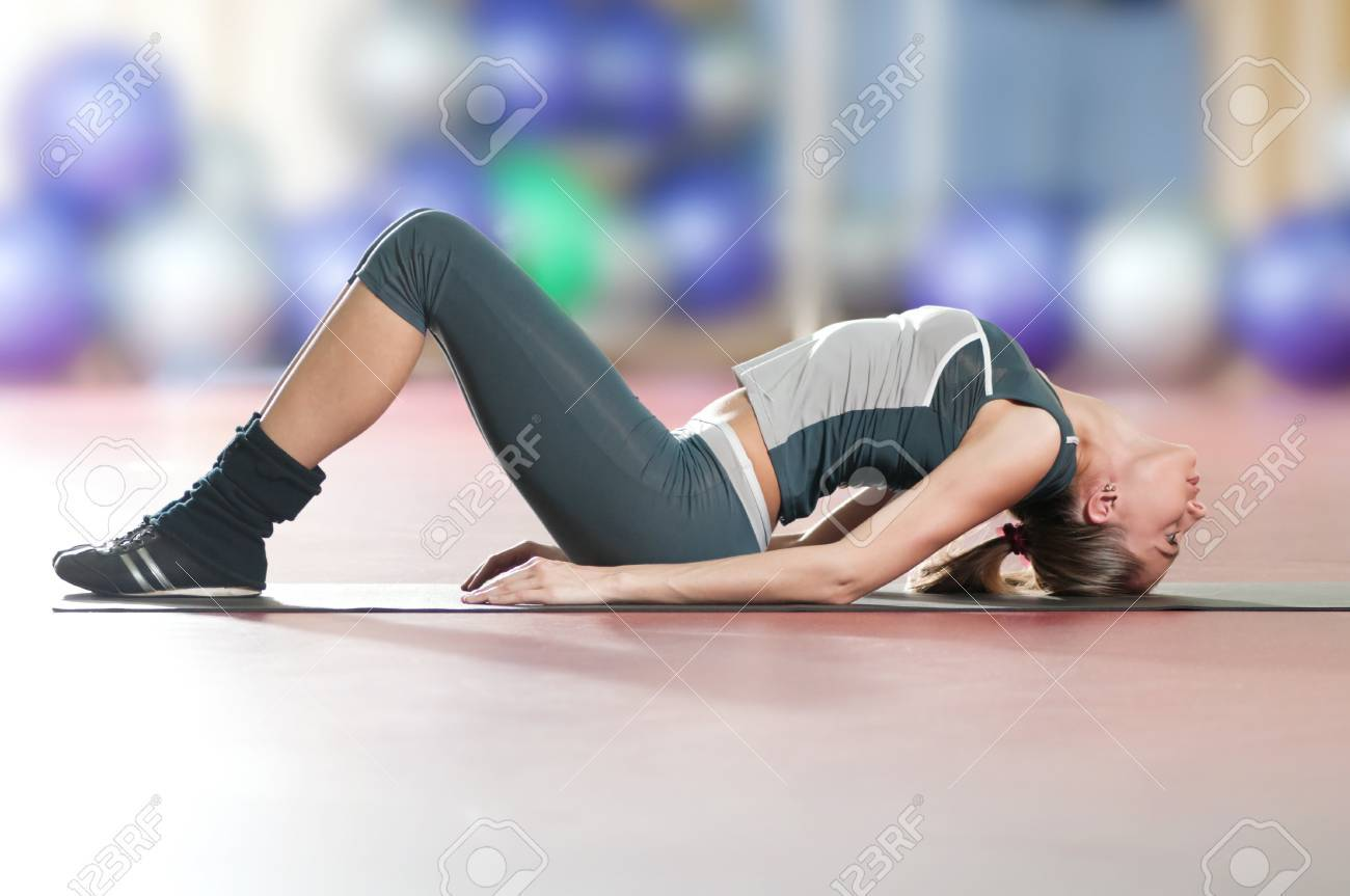 Beautiful sport woman doing stretching fitness exercise at sport gym. Yoga Stock Photo - 9805889