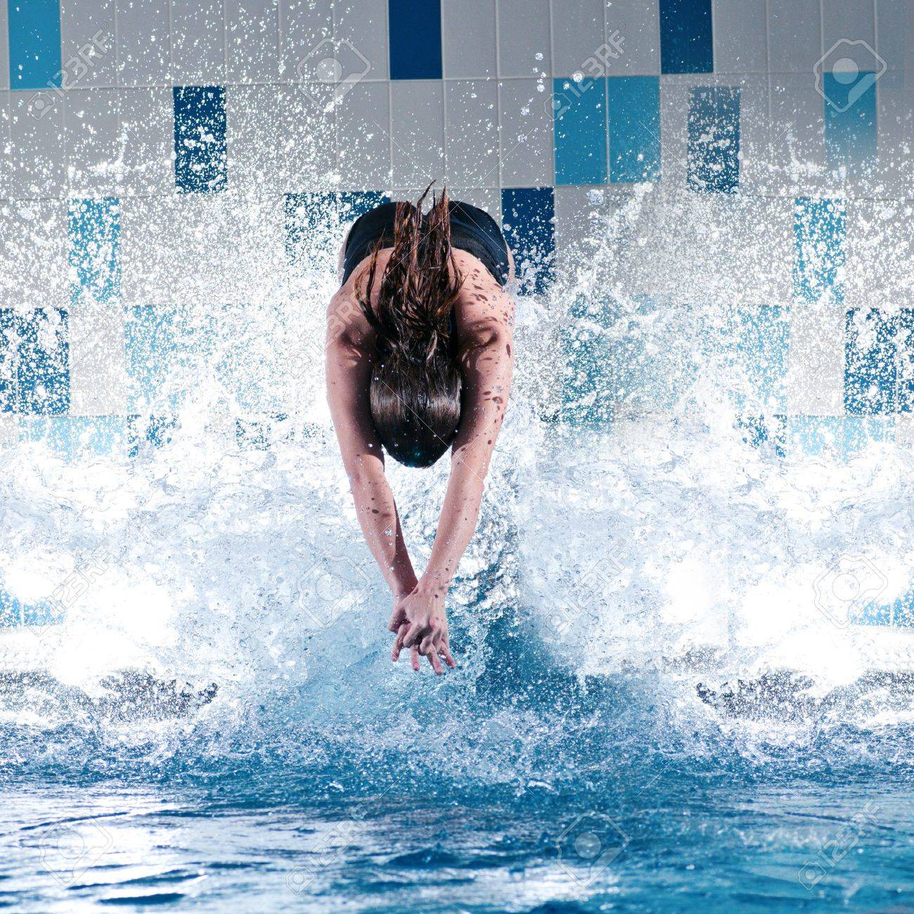 Portrait of a young woman jumping in swimming pool Stock Photo - 10000088