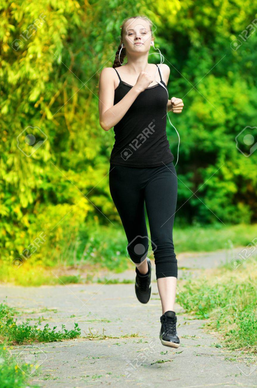 Beautiful young woman running in green park on sunny summer day Stock Photo - 10283434