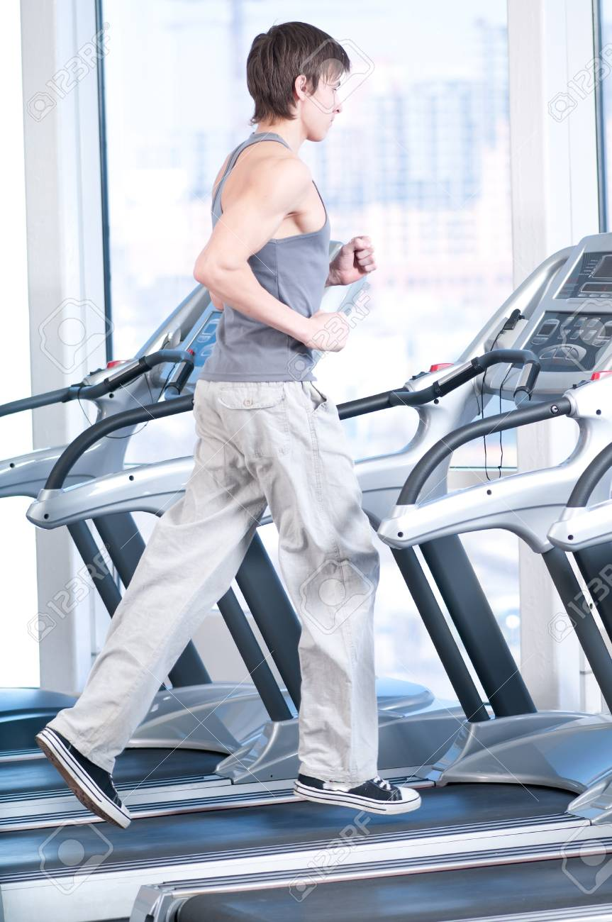 Young man at the gym exercising. Run on on a machine. Stock Photo - 10322836