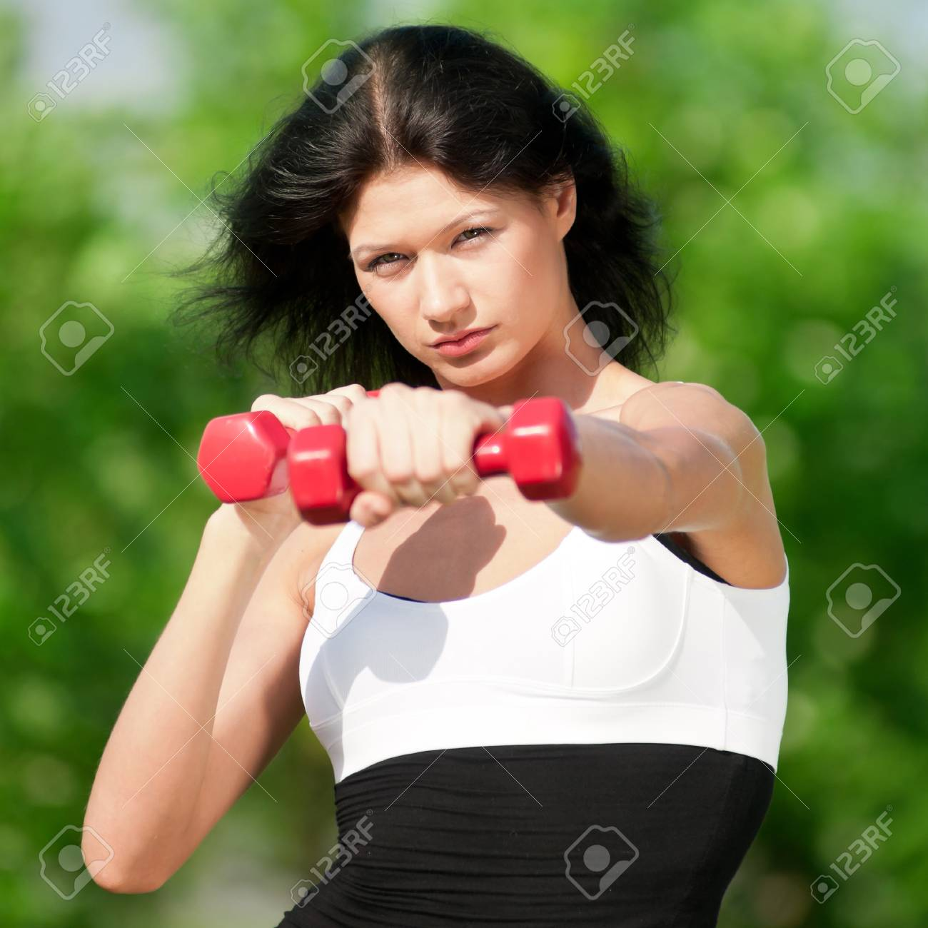 Young woman lifting small weights in the park Stock Photo - 10723864