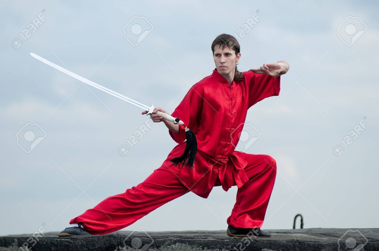 Shaolin warriors wushoo man in red with sword practice martial art outdoor. Kung fu Stock Photo - 11467464