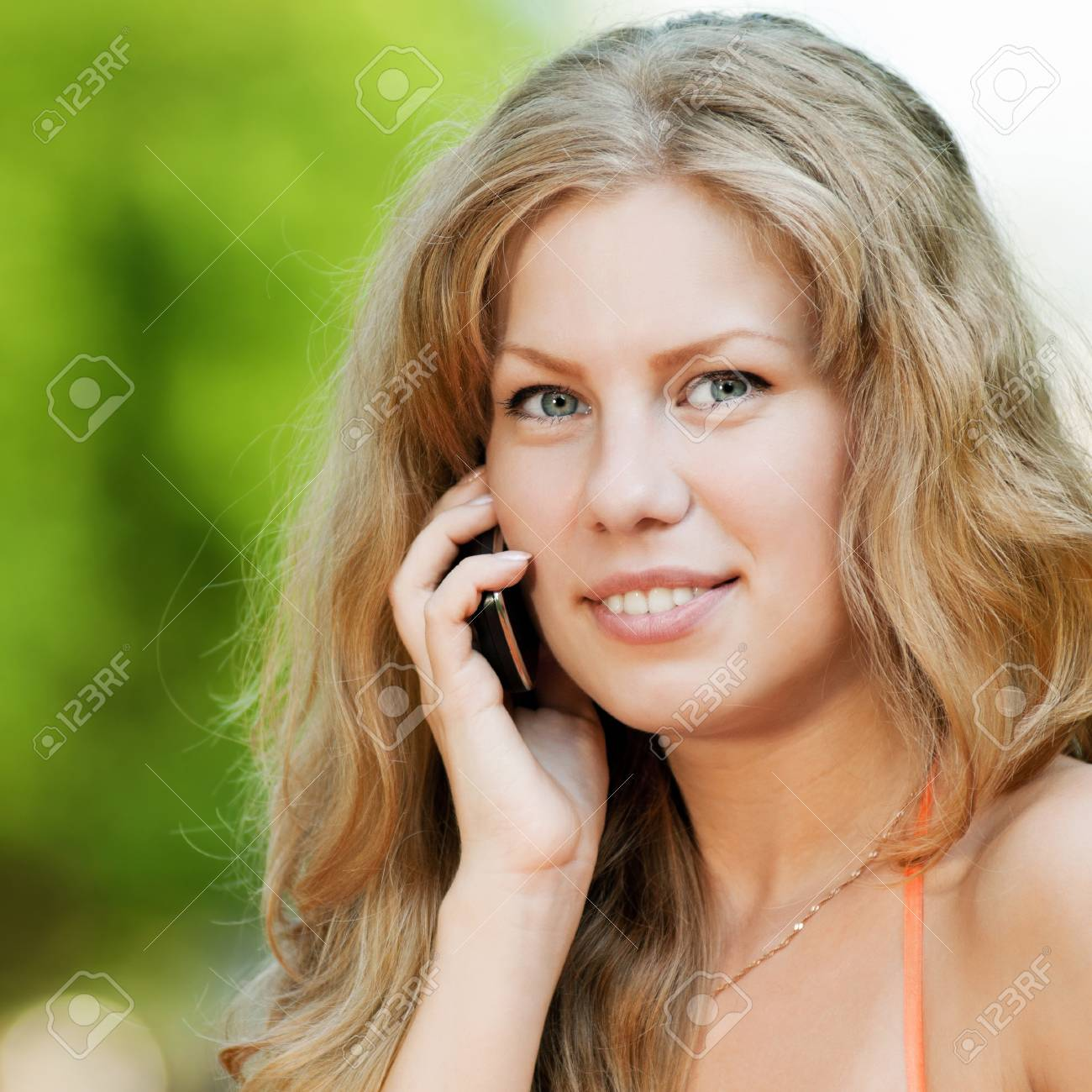 Young happy woman with mobile phone. SMS Stock Photo - 12535582