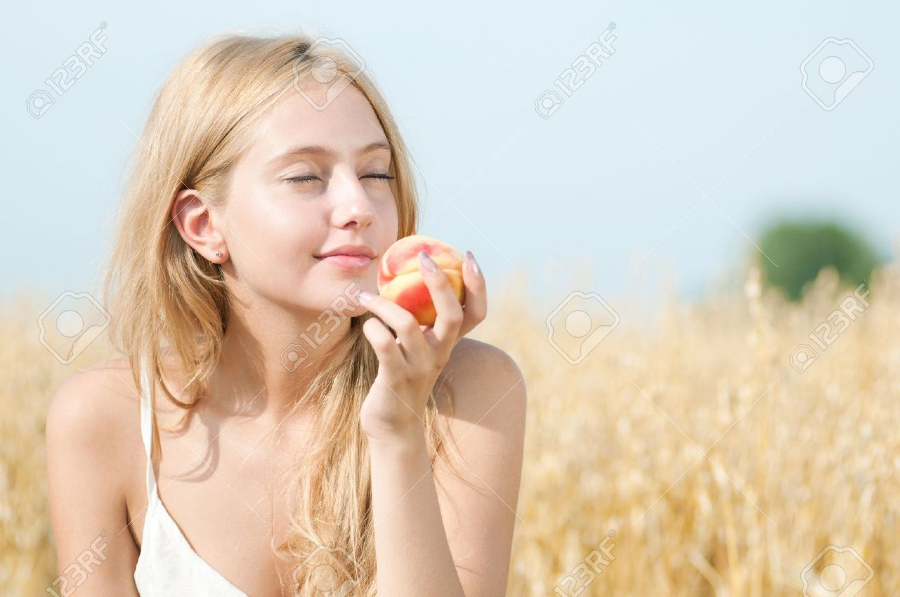 Young happy woman in wheat field with peach. Summer picnic Stock Photo - 12535659