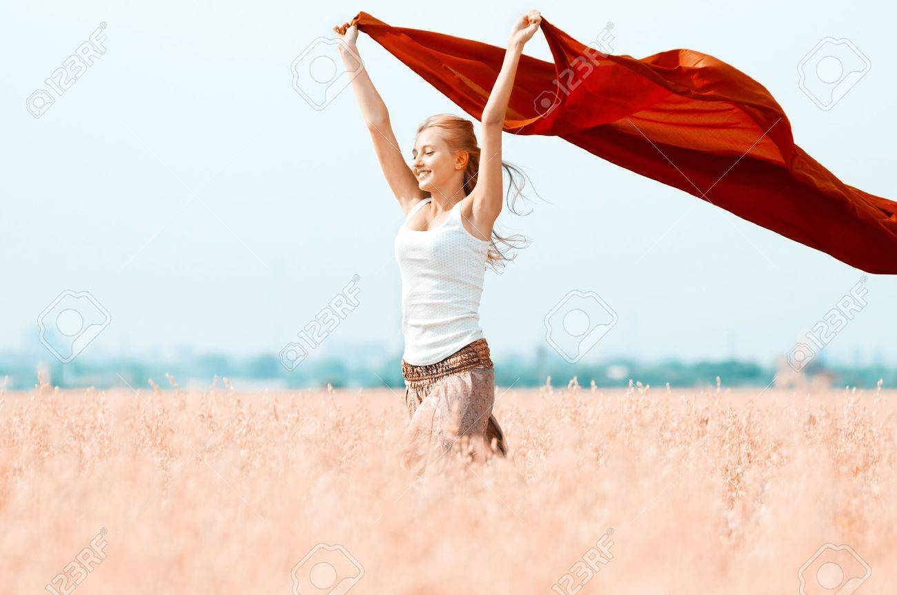 Young happy woman in wheat field with fabric. Summer picnic Stock Photo - 13303987