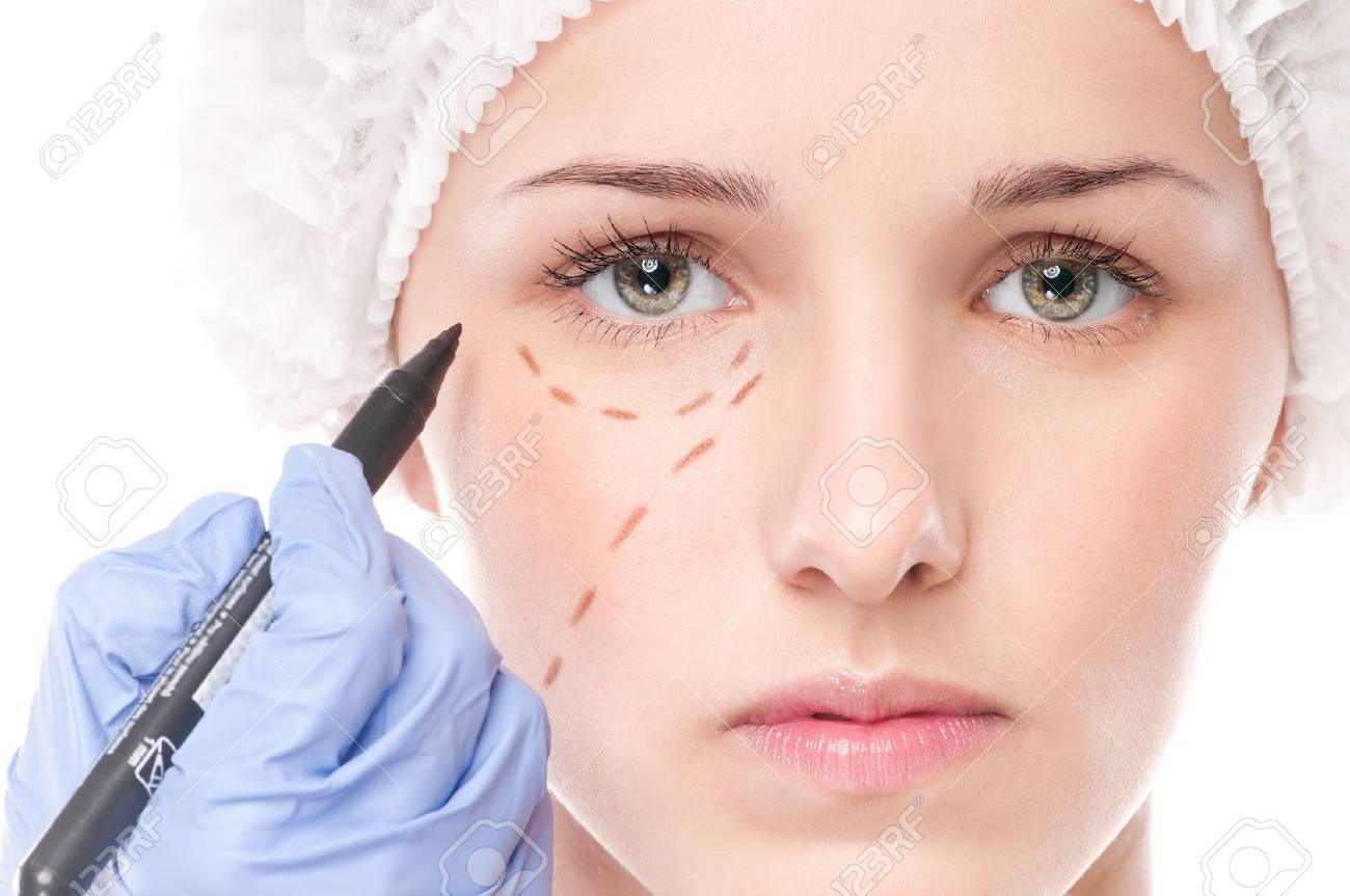 Beautician touch and draw correction lines on woman face. Before plastic surgery operetion. Isolated on white Stock Photo - 13622225