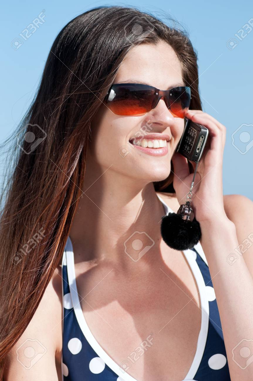 Young smiling woman talking by phone on a beach Stock Photo - 15262765