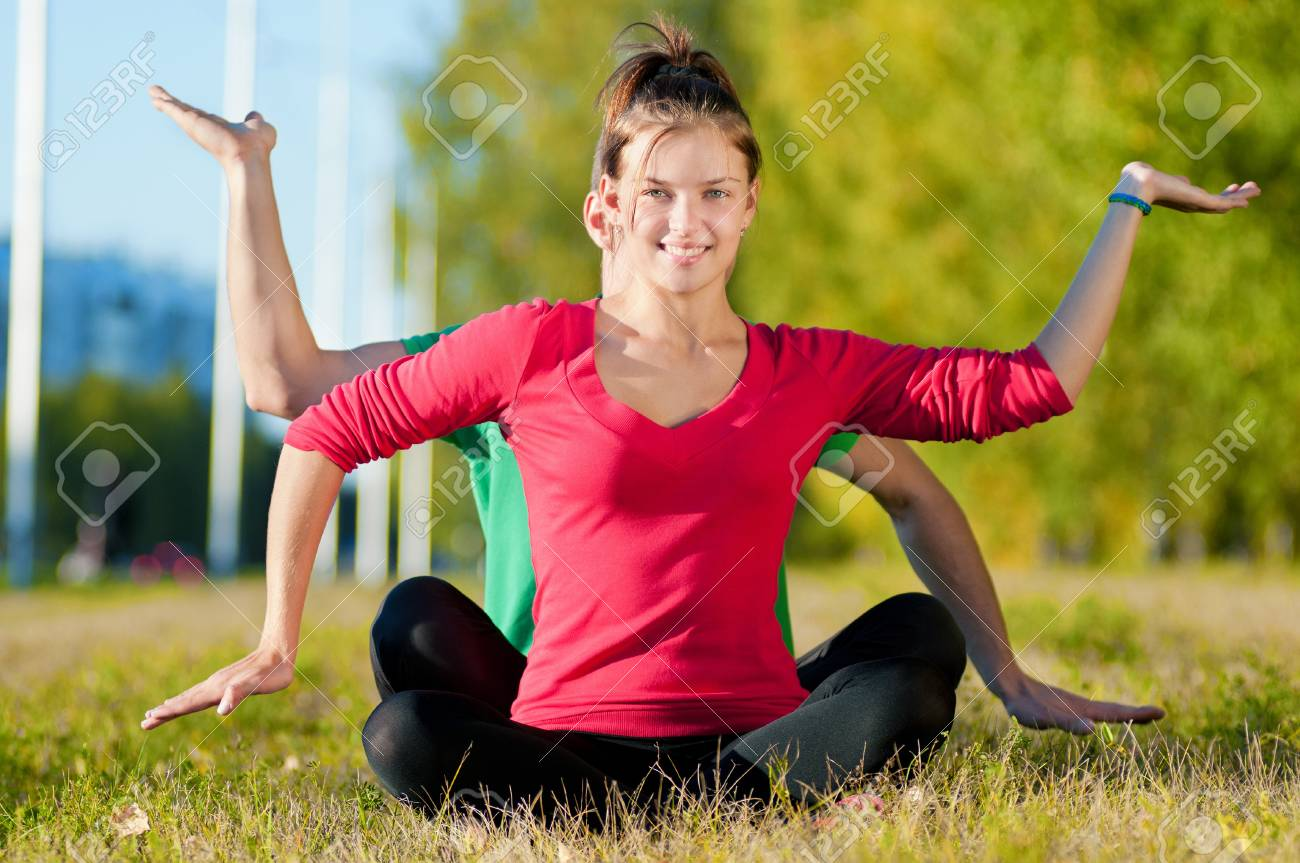 Young man and woman woman doing yoga in the sunny summer park Stock Photo - 15262749