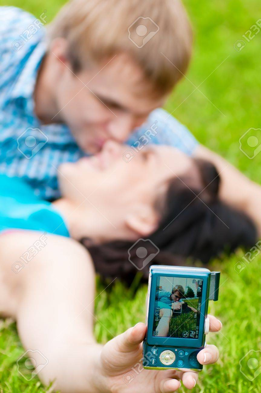 Young emotional happy teenage couple taking picture on grass in city park Stock Photo - 15620030