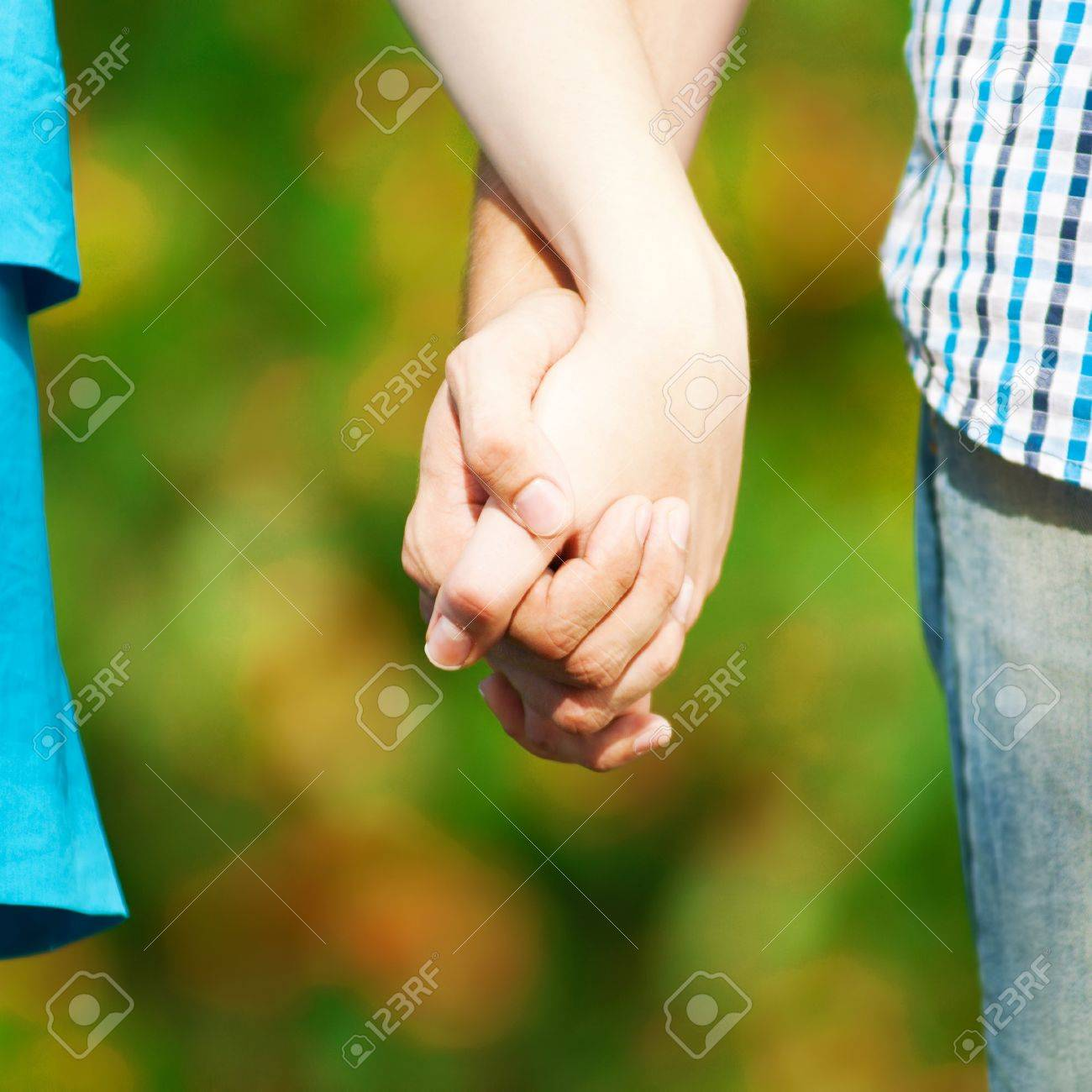 Concept shot of friendship and love of man and woman: two hands over green nature park Stock Photo - 15564011