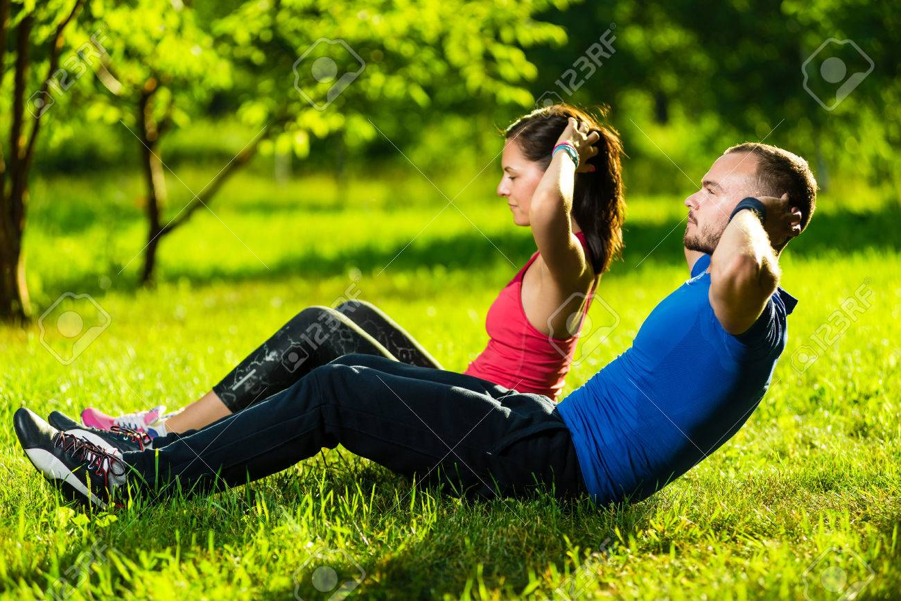 Man and woman exercising at the city park. Beautiful young multiracial couple. Sit ups fitness couple exercising outside in grass. Fit happy people working out outdoor. - 39993245